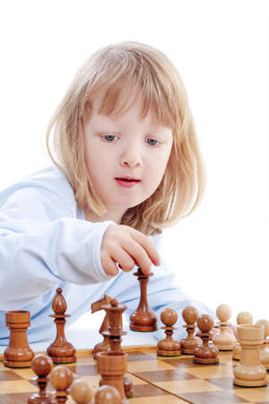 boy with long blond hair playing with chess pieces - isolated on white photo