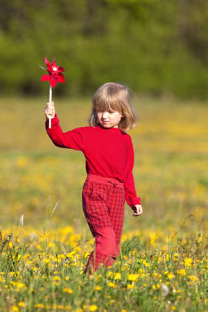 boy with long blond hair playing with pinwheels on a dandelion meadow photo