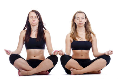 two young women sitting on the floor exercisng yoga - isolated on white photo