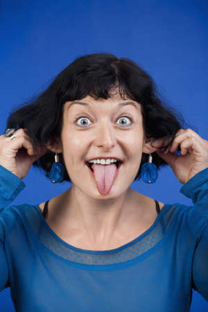 woman sticking out her tongue and pulling her ears - isolated on blue photo