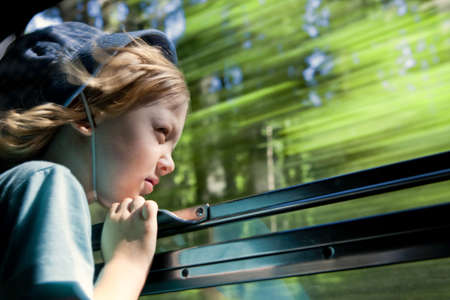 boy with long blond hair and hat looking out the train window Stock Photo