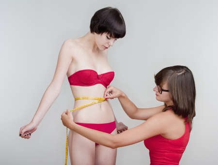 two young female friends measuring results of diet - isolated on gray Stock Photo