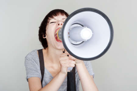 angry teenage girl yelling into a megaphone - isolated on gray