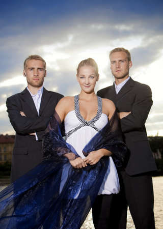 beautiful young blond woman standing outdoors accompanied by two bodyguards