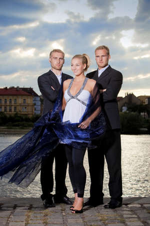 beautiful young blond woman standing outdoors accompanied by two bodyguards Stock Photo - 10518296