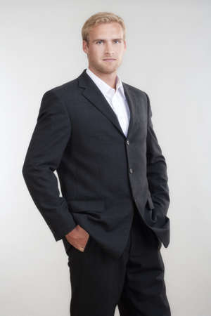 portrait of a young businessman with blond hair in suit standing - isolated on light gray