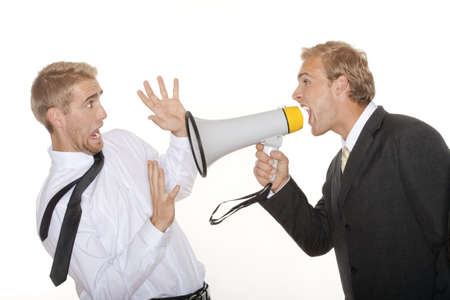 angry boss in suit yelling into a megaphone to scared employee - isolated on white