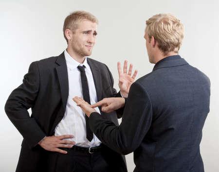 personas discutiendo: Dos hombres de negocios que de pie, hablando, discutiendo - aislados en gris claro