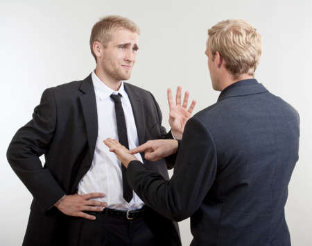 people arguing: Two you businessmen standing, discussing, arguing - isolated on light gray