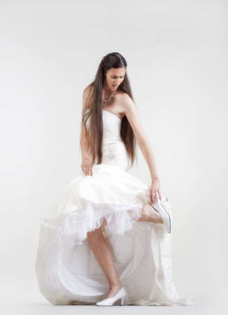long feet: bride in wedding dress taking off her shoe checking her hurting foot