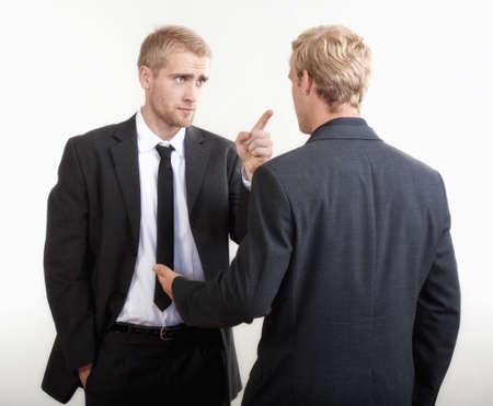 personas discutiendo: ywo que los hombres de negocios de pie, hablando, discutiendo - aislados en gris claro