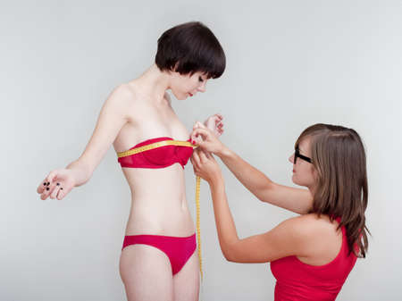 two young female friends measuring results of diet - isolated on gray photo