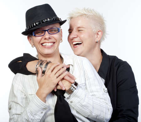 homosexual couple: two lesbian woman with punk hairstyle laughing - isolated om white