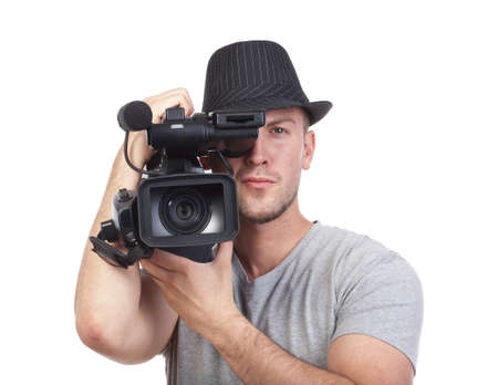 professional videographer in hat holding a camera - isolated on white