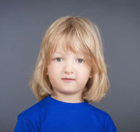 studio portrait of a boy with long blond hair - isolated on gray photo