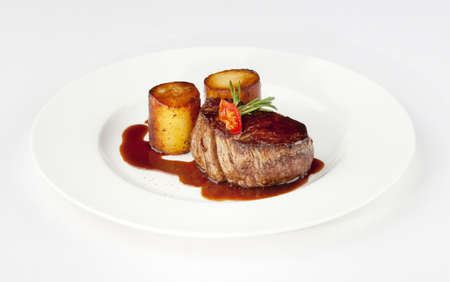 beef filet with fondant potato and red wine sauce on a white plate photo