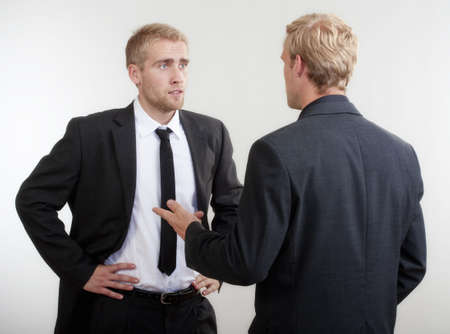 two face: ywo you businessmen standing, discussing, arguing - isolated on light gray Stock Photo