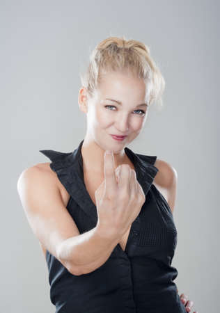 sexy blond girl showing come on gesture looking, smiling - isolated on gray Stock Photo - 10997375
