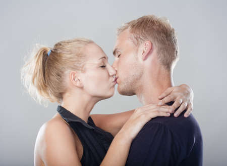 young happy couple embracing, kissing - isolated on light gray photo