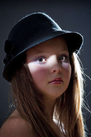 12: dramatic portrait of a twelve years old girl with hat Stock Photo