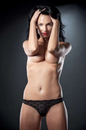 beautiful woman with dark hair in sexy black underwear over gray