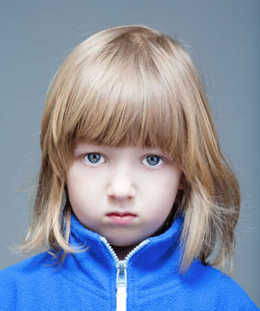 portrait of a boy with long blond hair in blue top - isolated on gray