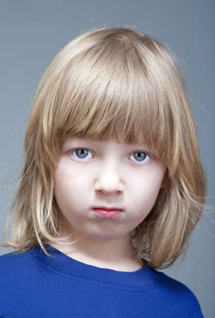 portrait of a boy with long blond hair in blue top - isolated on gray photo