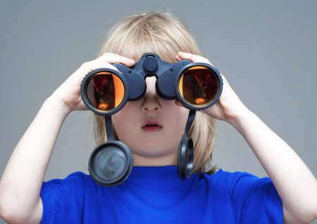 boy with long blond hair looking through binaculars - isolated on gray Stock Photo - 13450928