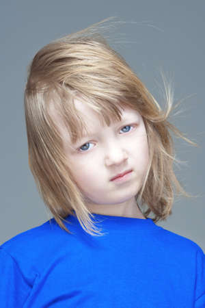 portrait of a sad boy with long blond hair in blue top - isolated on gray photo