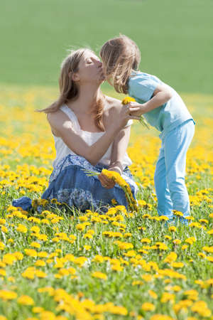 mother and son kissing on dandelion field in spring photo