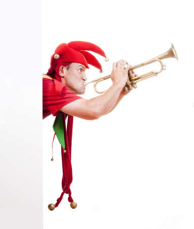 entertaining: jester - entertaining figure in typical costume blowing trumpet