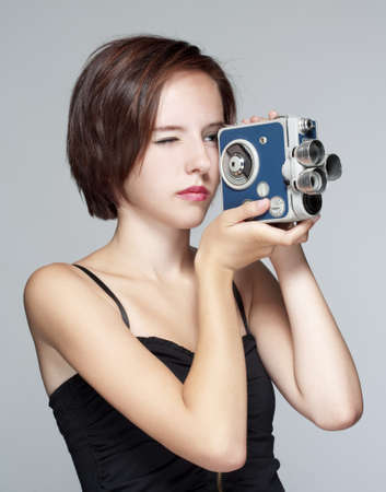 teenage girl with an old film camera - isolated on gray photo