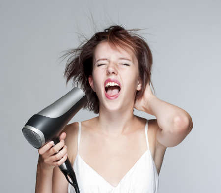 beautiful teenage girl blowing her hair with hairdryer, screaming - isolated on gray Stock Photo