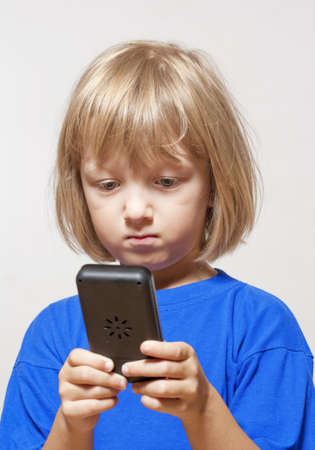handheld computer: boy playing with handheld computer game - isolated on light gray