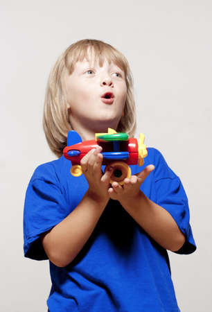 boy with long blond hair playing with toy airplane - isolated on light gray photo