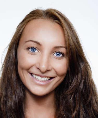 ojos azules: retrato de una mujer joven hermosa con el pelo castaño y ojos azules sonriendo