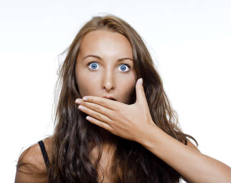 surprised and shocked girl covering moth with her hand - isolated on white Standard-Bild