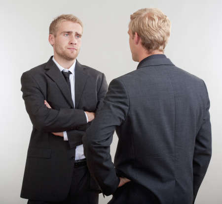 two people talking: two young businessmen standing, discussing, arguing - isolated on light gray Stock Photo