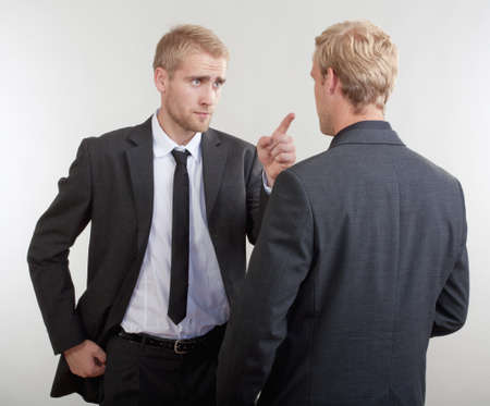 two young businessmen standing, discussing, arguing - isolated on light gray photo