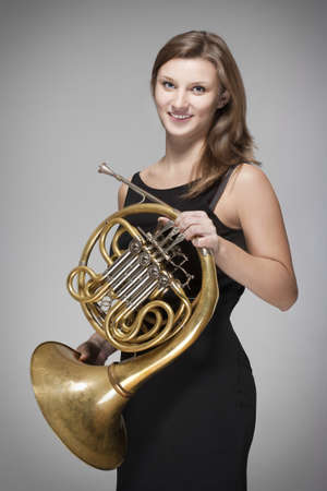 french horn: young female musician with concert french horn in black dress Stock Photo