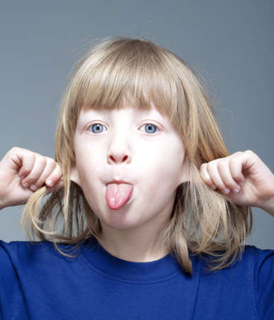 long tongue: boy with long blond hair sticking out his tongue and pulling ears