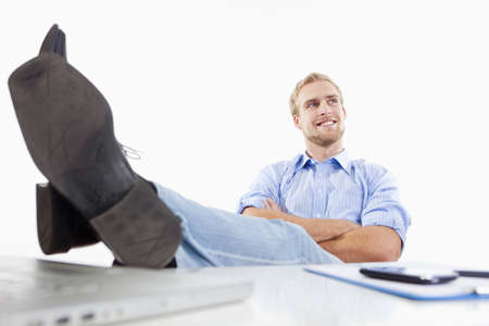 relaxed young man at office with his feet on the desk photo