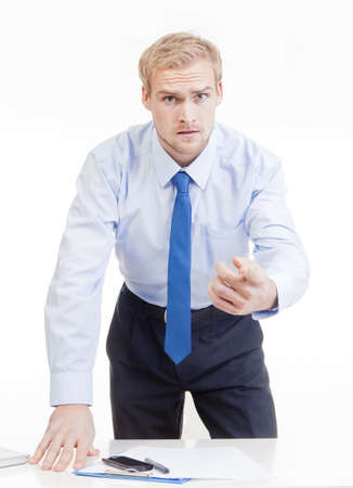 gesticulating: angry boss standing behind desk, gesticulating, accusing, blaming Stock Photo
