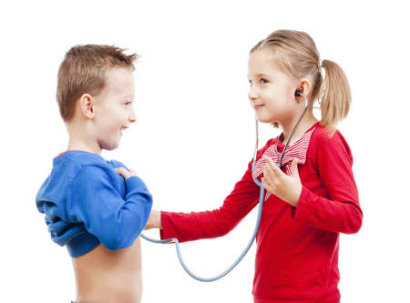 brother and sister playing a doctor with stethoscope - isolated on white photo