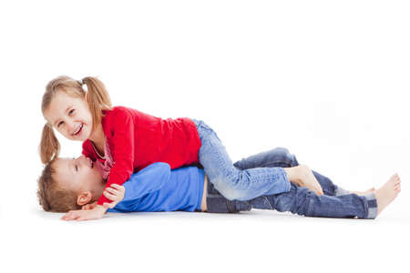 brother and sister having fun with each other - isolated on white Stock Photo