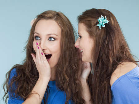 two young female friends whispering gossip - isolated on blue photo