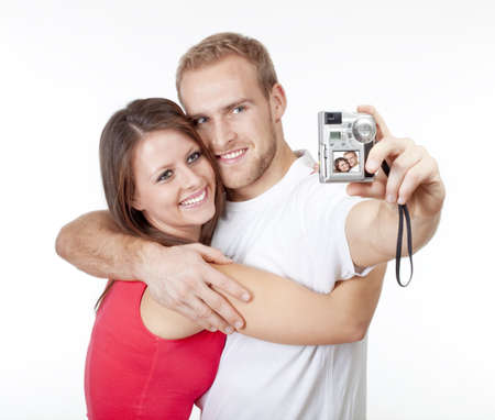 happy young couple taking pictures of themselves - isolated on white Standard-Bild