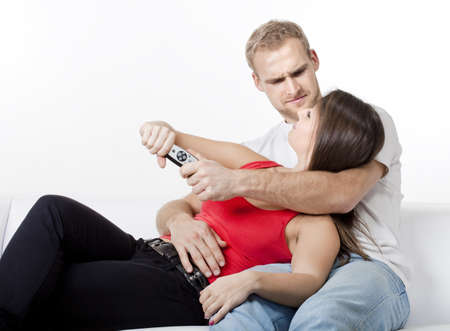 young couple watching television, fighting over remote control photo