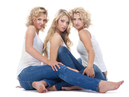 three young women sitting on the floor, looking - isolated on white photo