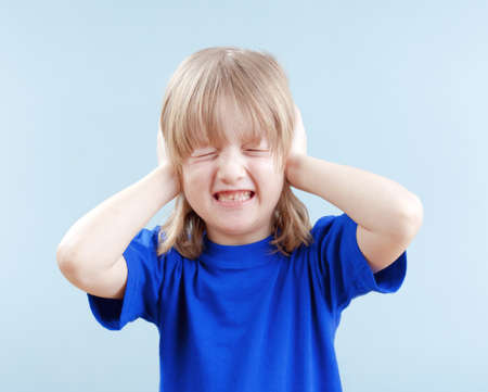 upset boy with long blond hair covering his ears as protection - isolated on blue Stock Photo - 19126353